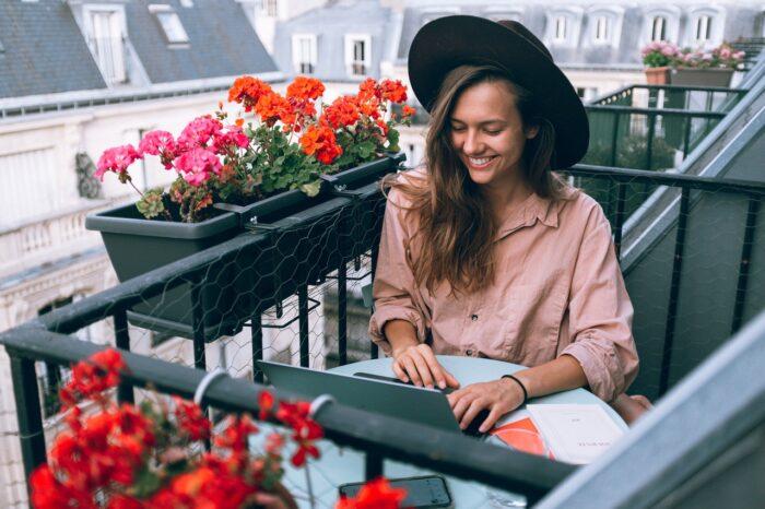 Jovem acessa o notebook sorridente, na varanda. A presença digital. alinhada com a proximidade e empatia são importantes fatores para a decisão de consumo entre as novas gerações.